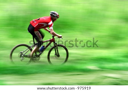 mountain bike race in a forest in denmark,  Shot with low shutter speed to achieve motion blur - stock photo