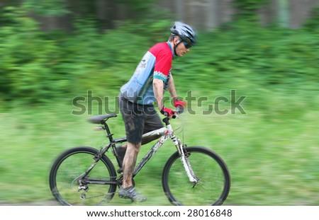 mountain bike racer. motion blur - stock photo