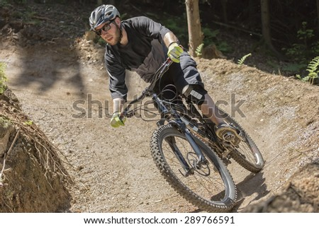 Mountain bike rider rides through a gravity slope of an artificial dirt track. The scene is held in earthy colors. - stock photo