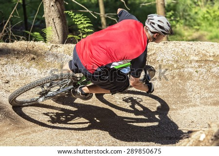 Mountain bike rider rides through gravity slope of an artificial dirt track. - stock photo