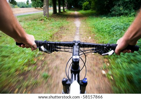 Mountain bike rider riding real fast, motion blur - stock photo
