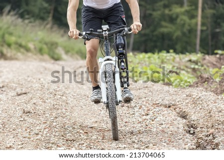 Mountain bike rider with leg prosthesis rides a gravel track  - stock photo