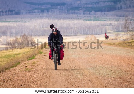Mountain bike rides along the winding dirt road in the high mountains - stock photo