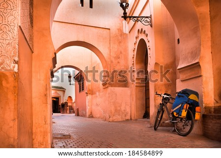 mountain bike standing near a red wall in the Muslim city of Marrakech in the street with beautiful arches and walls, ornamented tiles. - stock photo