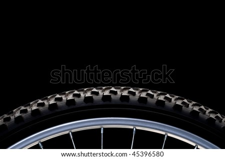 Mountain bike tire and rim on black with copy space - stock photo