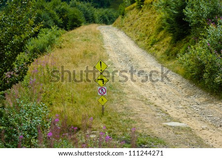 Mountain bike track and warning signs - stock photo