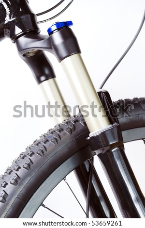 Mountain bike wheel with suspension fork on white background - stock photo