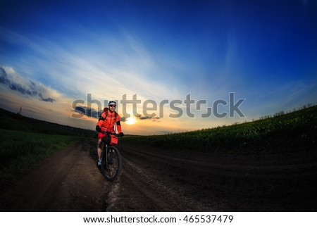 Mountain bikeer rides on the trail against beautiful sunset