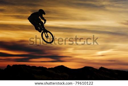 Mountain biker at jump against nice sunset - stock photo