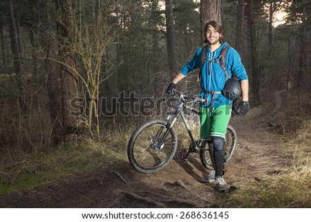 Mountain biker cycling standing by an off road trail through the woods in the late afternoon - stock photo