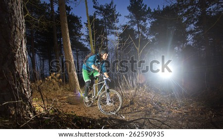 Mountain biker cycling through the woods on an off road trail at sunset. Backlit image - stock photo