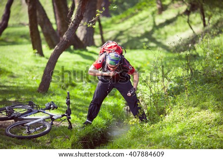 Mountain biker drinking water from a spring - stock photo
