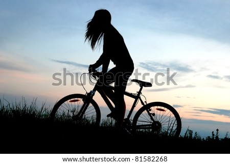 mountain biker girl in sunrise - stock photo
