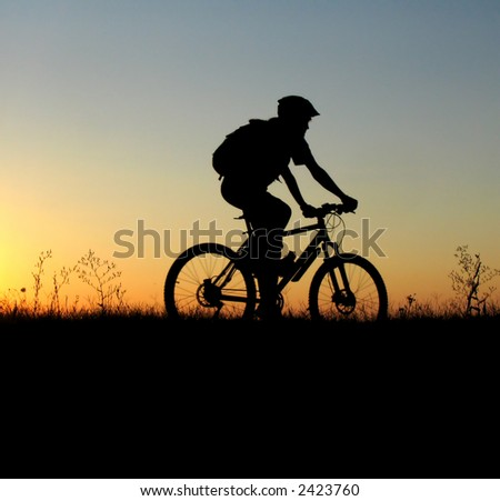 mountain biker girl silhouette in sunrise - stock photo