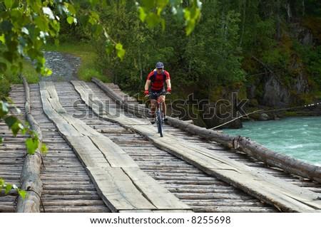 Mountain biker goes on old wooden bridge - stock photo