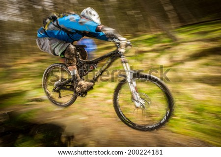 Mountain biker going over a jump in the forest with speed - stock photo