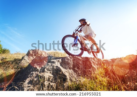 Mountain biker in action across rocks against blue sky concept for healthy lifestyle, exercise and extreme sports - stock photo