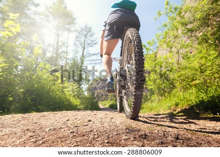 Mountain biker in action on a forest trail concept for healthy lifestyle, exercise and extreme sports - stock photo