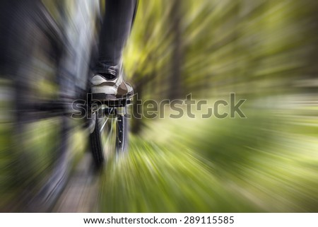 Mountain biker in the forest, zoom burst effect - stock photo