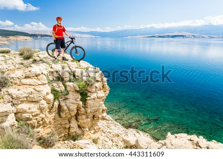 Mountain biker looking at view and traveling on bike in summer sea landscape. Man rider cycling MTB on country road or single track. Fitness motivation in beautiful inspirational view, Croatia. - stock photo