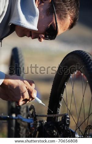 Mountain biker lubricate bicycle chain - stock photo