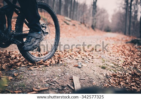 Mountain biker on cycle trail in woods. Mountains in winter or autumn landscape forest. Man cycling MTB on rural country road. Sport fitness motivation and inspiration. Selective focus on pedal. - stock photo