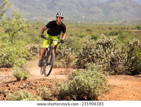 Mountain Biker on Desert Trail with Dust Behind Wheel - stock photo