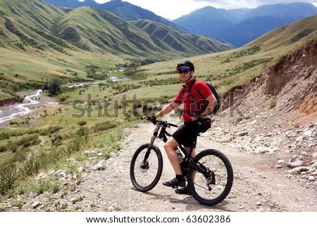 Mountain biker on old rural road - stock photo