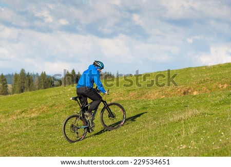 mountain biker on sunny day rolls on the rolling hills of green forest against the blue sky with beautiful clouds