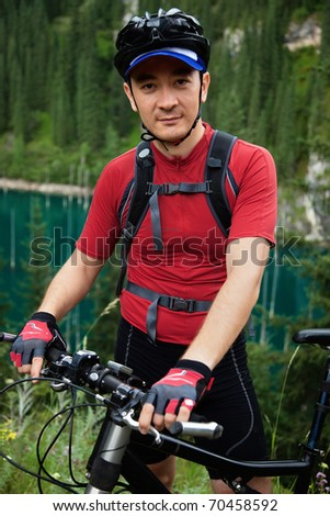 Mountain biker portrait beside lake - stock photo