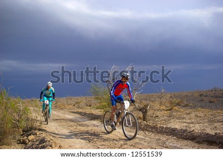 Mountain biker racing on old road in desert - stock photo