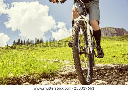 Mountain biker rides a trail in the mountains - stock photo