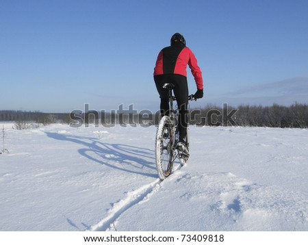 Mountain biker riding a snowy trail in winter - stock photo