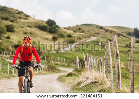 Mountain biker riding on bike in summer mountains landscape. Man cycling MTB enduro on rural country road. Sport fitness motivation and inspiration. - stock photo