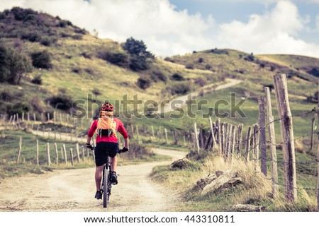 Mountain biker riding on bike in summer or fall mountains landscape. Man cycling MTB on rural country road. Travelling, sport fitness motivation in inspirational landscape. - stock photo