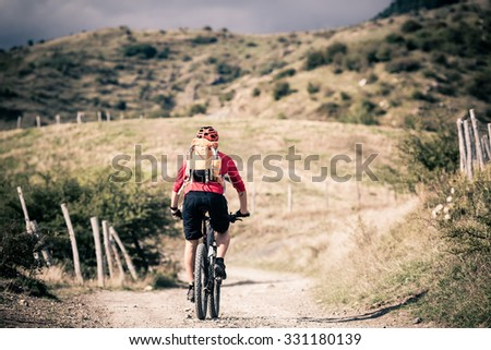 Mountain biker riding on bike singletrack trail in autumn mountains. Man rider cycling MTB on rural road or single track. Sport fitness motivation and inspiration in beautiful inspirational landscape. - stock photo