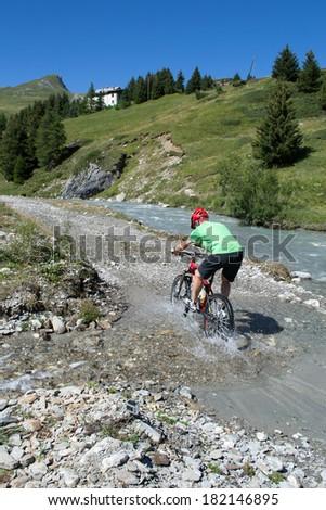 Mountain biker riding through stream in Swiss mountain area with water splashing - stock photo