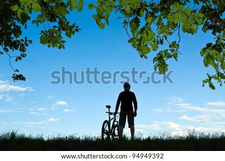 Mountain biker silhouette in summer nature - stock photo