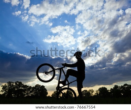 Mountain biker silhouette in summer over blue cloudy sky - stock photo