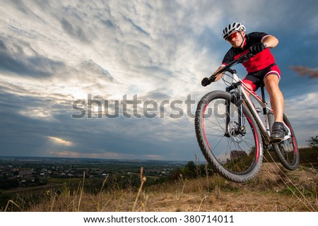Mountain biker with helmet jumping against blue evening sky. Low angle portrait. Extreme sport donwhill cyclist - stock photo