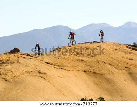 Mountain bikers climb rugged slickrock in Moab, Utah - stock photo