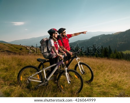 mountain bikers on a meadow, along bike, looking at the beautiful landscape - stock photo