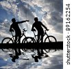mountain bikers  silhouette in sunset - stock photo