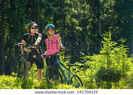 Mountain bikers standing and resting in forest sunny nature - stock photo