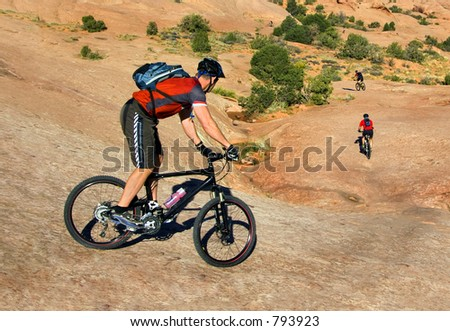 Mountain bikers tackle challenging conditions near Moab, Utah - stock photo