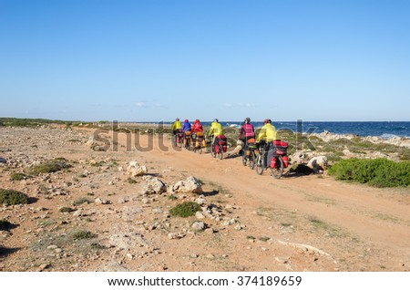 Mountain bikes rides along the winding dirt road along the sea - stock photo