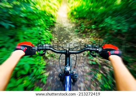 Mountain biking down hill. View from biker. - stock photo