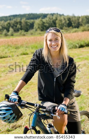Mountain biking happy sportive girl relax in meadows sunny countryside - stock photo