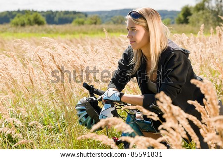 Mountain biking happy young woman relax in cornfield sunny countryside - stock photo