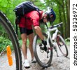Mountain biking in a forest - bikers on a forest biking trail (shallow DOF, focus on the bike wheel in the foreground) - stock photo